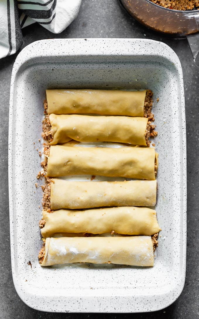 This Meat Cannelloni with Creamy Tomato Béchamel has homemade pasta is encased around a melt-in-your-mouth veal, pork, and chicken filling, it's covered in tomato sauce, creamy béchamel, and dusted with parmesan.