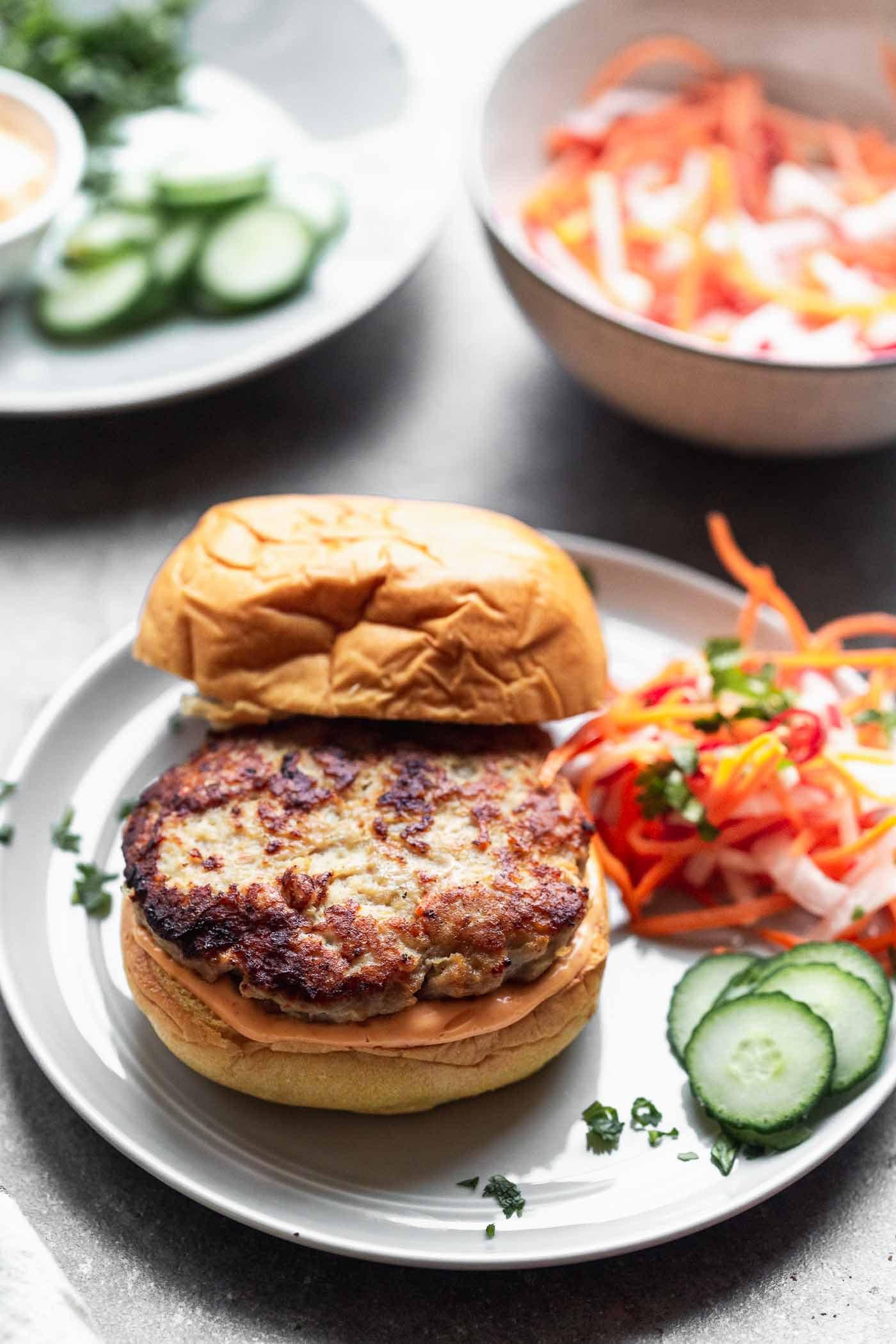 Bánh Mì Chicken Burgers are a burger take on a classic. A ground chicken patty is packed with all the flavors of a classic Bánh Mì sandwich, topped with sweet and spicy pickled veggies, a zippy sriracha mayo, and sandwiched between a toasted brioche bun.