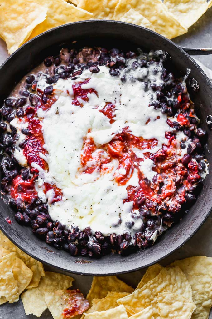 Chipotle Raspberry Black Bean Dip is sweet, spicy, and the most addictive appetizer on the planet. It's packed with a homemade raspberry chipotle sauce, tangy cream cheese, heart black beans, and gooey Monterrey jack cheese. Serve with tortilla chips and watch it disappear.