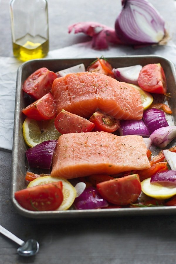 Salmon filets on top of tomatoes, red onion and lemon