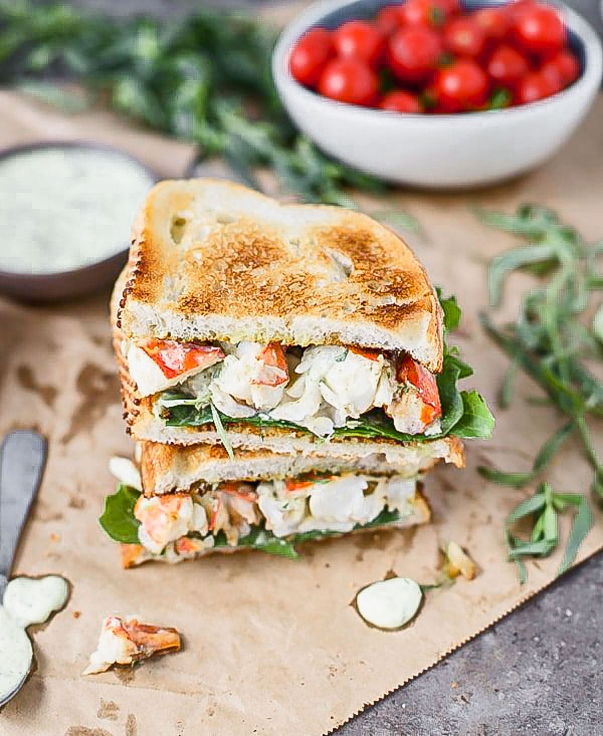 Our Green Goddess Lobster Sandwich Recipe is a dressed-up version of a classic lobster roll. We toss perfectly cooked buttery lobster with a quick green goddess dressing studded with fresh tarragon, basil, and green onion. We pile it high on toasted sourdough bread and top it off with peppery arugula and a squeeze of lemon.