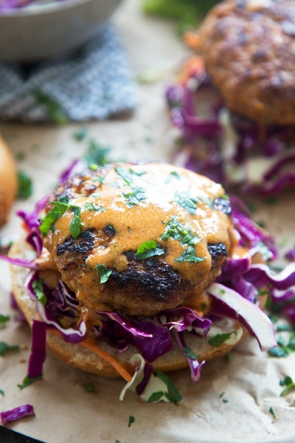 These Coconut Red Curry Burgers are irresistibly juicy on the inside, crispy on the outside and our new favorite way to eat a burger. The patties are also FULL of flavor, with hints of garlic, ginger, red chile paste and loads of coconut. Each crispy patty is topped with an super simple coconut curry sauce, lots of zippy slaw and nestled into a soft bun.