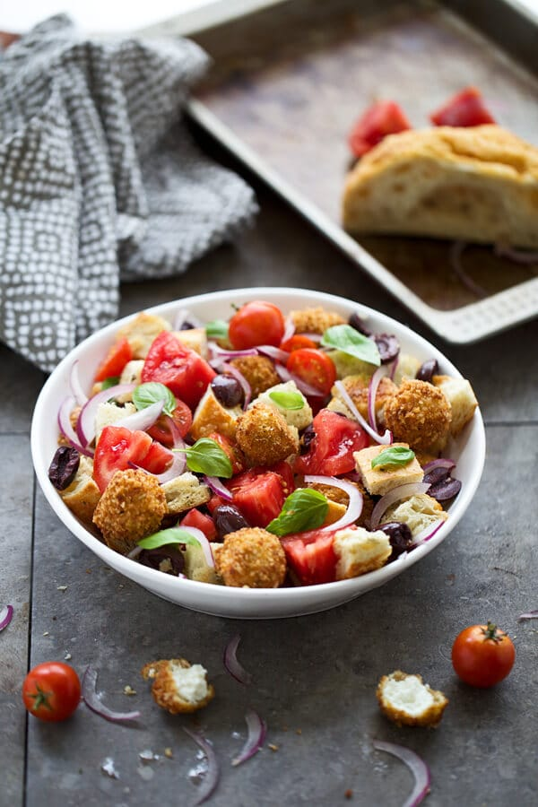 Panzanella salad with fried goat cheese in a round white bowl