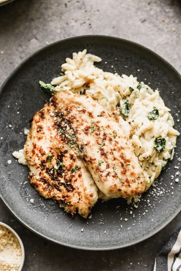 Parmesan Broiled Tilapia is one of our go-to meals because it requires minimal ingredients, all of of which you likely have in your pantry, and takes less than 30 minutes to whip up, from start to finish. We take flaky tilapia filets and smother them in a butter and parmesan paste laced with hot sauce, then pop them under the broiler until they have an irresistible golden crust.