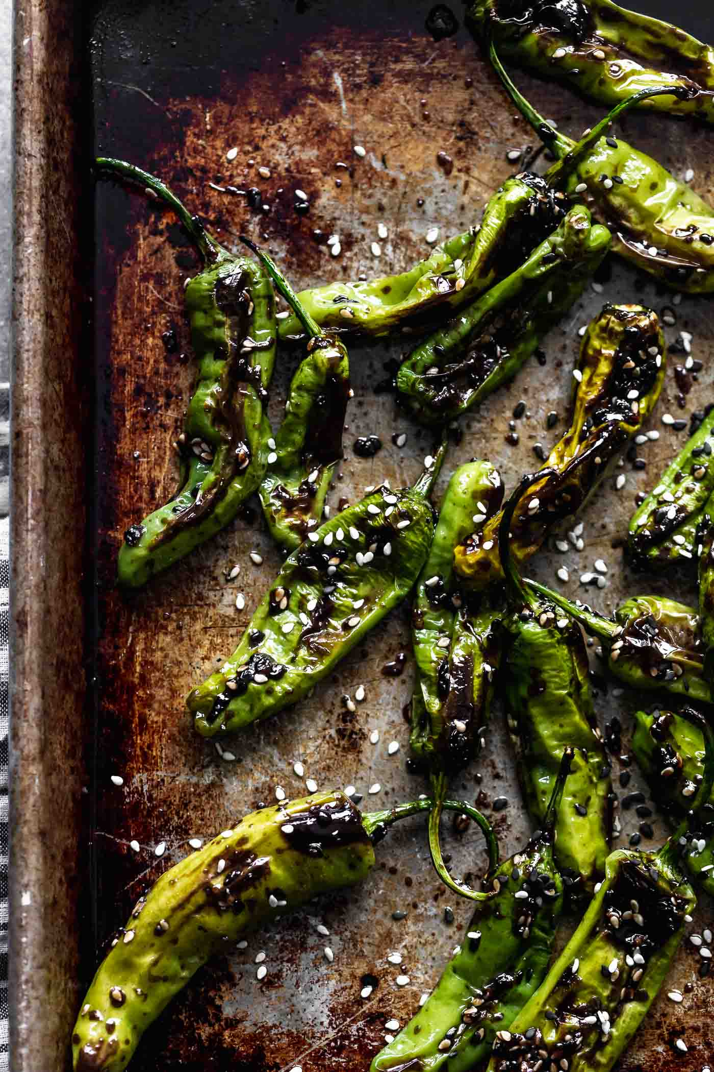 These Roasted Shishito Peppers with Soy Glaze are the perfect blend of sweet, spicy and savory. Each pepper is charred under the broiler, then tossed in an easy soy-based glaze, sesame seeds and a little bit of orange peel. The perfect snack!