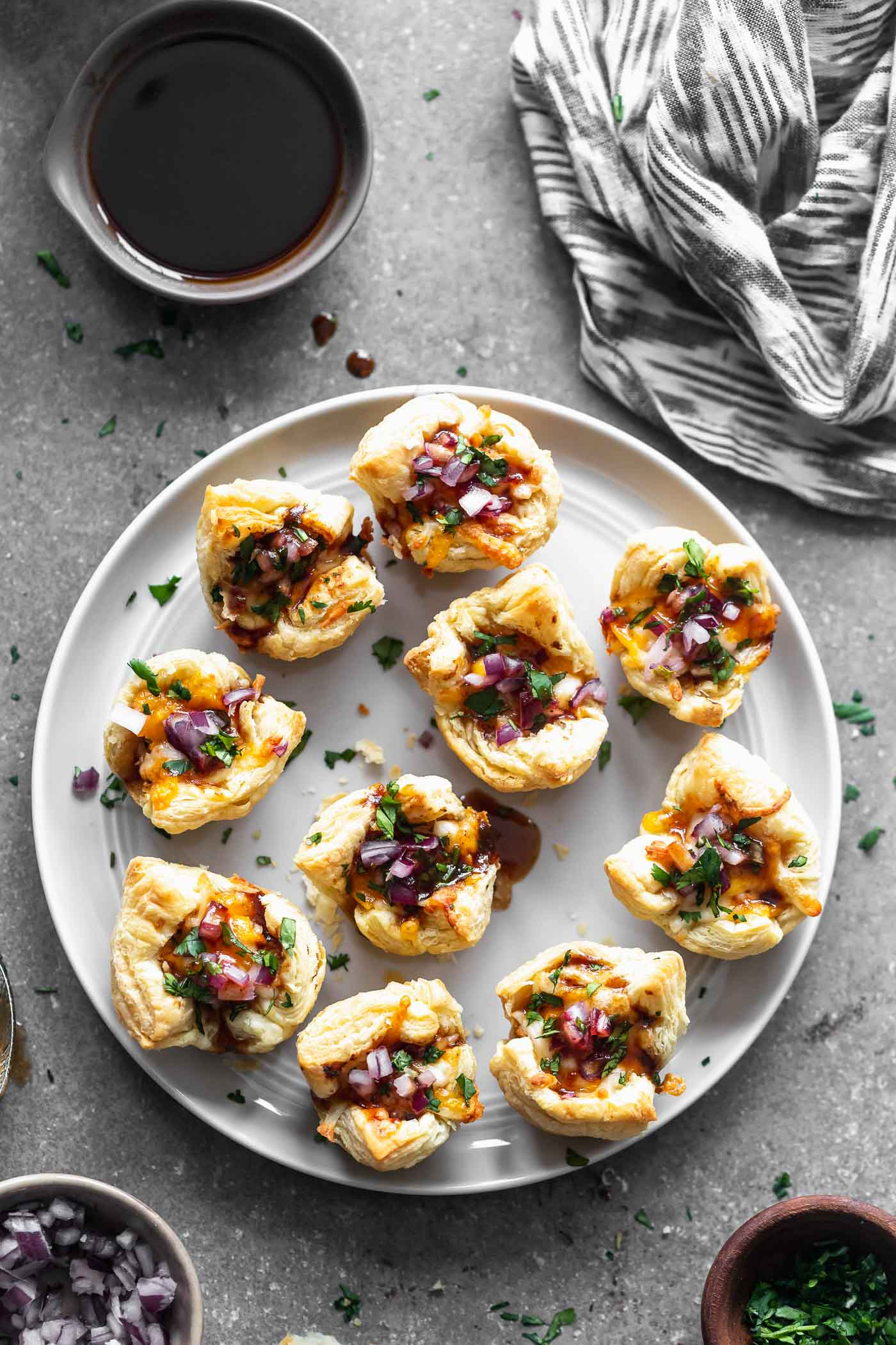 Cheesy Barbecue Chicken Bites: Chopped chicken tossed in your favorite barbecue sauce, covered in cheese and served with chopped red onion and cilantro. The perfect bite-sized appetizer for a crowd!
