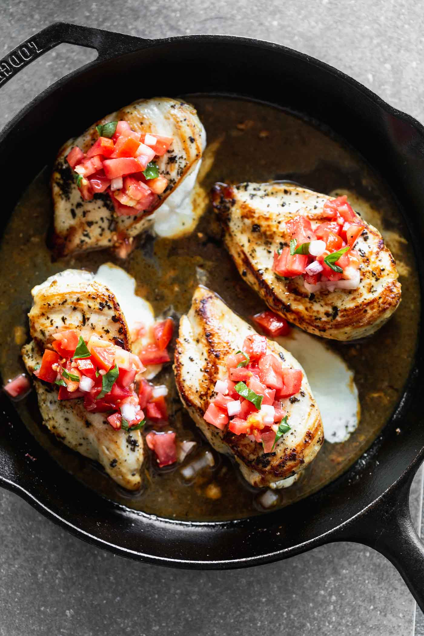 This Cheesy Lemon Chicken with Bruschetta Topping is stuffed with gooey mozzarella cheese, served with an easy pan sauce, and a fresh tomato topping.