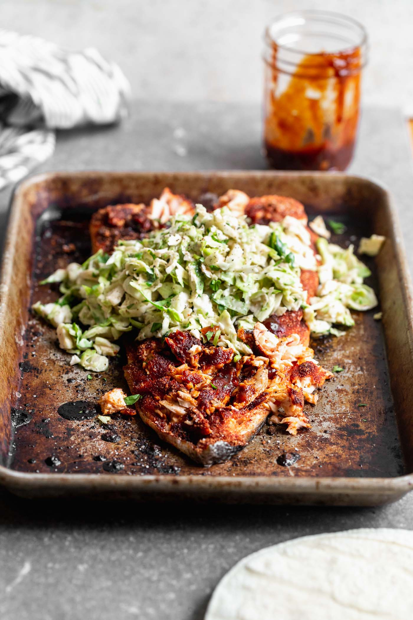 This Baked BBQ Salmon with Brussels Sprout Slaw is one of our favorite ways to serve salmon! We press a sweet and spicy dry rub on the surface of the fish, bake until crispy on the outside and buttery on the inside. We slather the salmon with homemade barbecue sauce and top with a cool, crisp Brussels sprout slaw. Serve as is, or nestle into tortillas for the perfect taco.