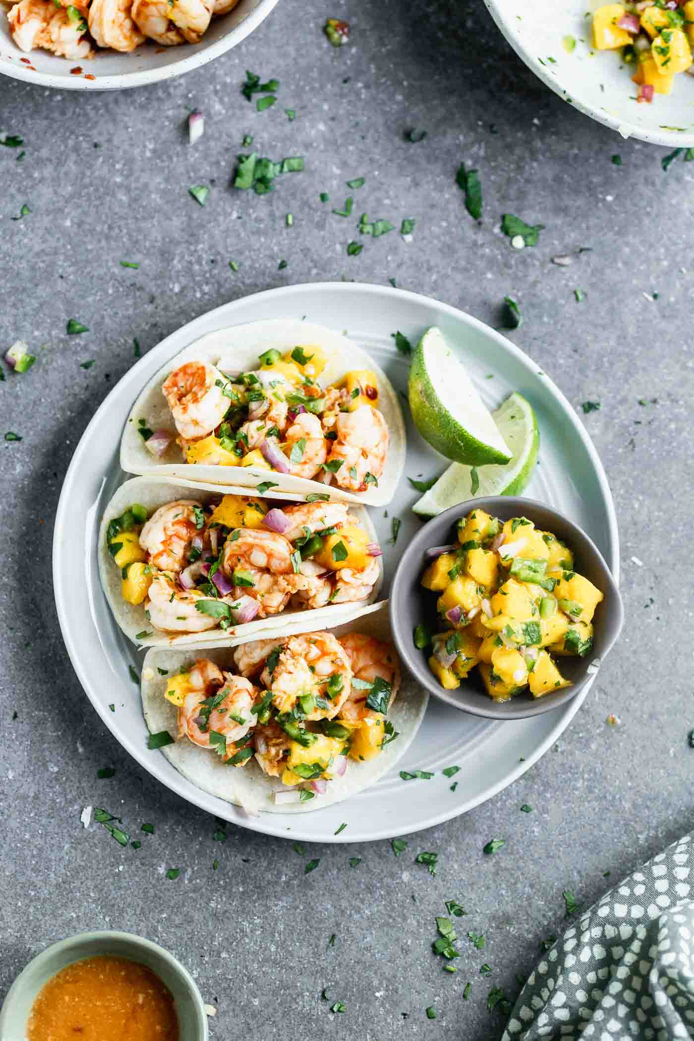 These Easy Chipotle Shrimp Tacos with Mango Salsa are perfect for breezy summer lunches, healthy dinners, or any kind of celebration. Plump shrimp are flavored with chipotle peppers, lime juice, and honey, baked and nestled into corn tortillas (or lettuce wraps!). Each taco is topped off with a quick homemade mango salsa, a little bit of cilantro, and ready to be served!