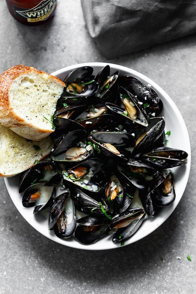These 5-Ingredient Steamed Beer Mussels are the easiest, most delicious was to prepare mussels! All you need is beer, garlic, a little bit of butter, heavy cream, and of course mussels! We also talk about how to store, clean, and prepare them so they're perfect every time!
