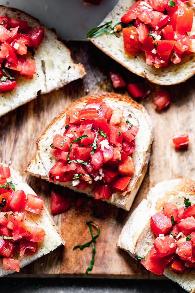 Tomato Basil Bruschetta is a classic Italian appetizer, and something everyone should make when tomatoes are at their peak. This version is completely authentic with just tomatoes, basil, olive oil, and a little bit of salt and pepper to season the tomatoes. It's served with crusty Italian bread, and that's it!