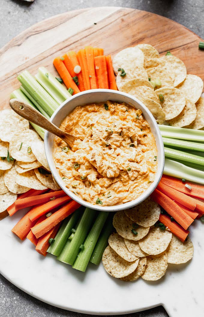 This Healthy Buffalo Chicken Dip (without cream cheese) is the perfect way to get you buffalo Game Day fix without all the fat and calories. Greek yogurt is simmered with sautéed onion and garlic, buffalo sauce, a little bit of blue cheese, a touch of mayo, and plenty of tender shredded chicken. Serve with carrots, celery, and your favorite baked chips.