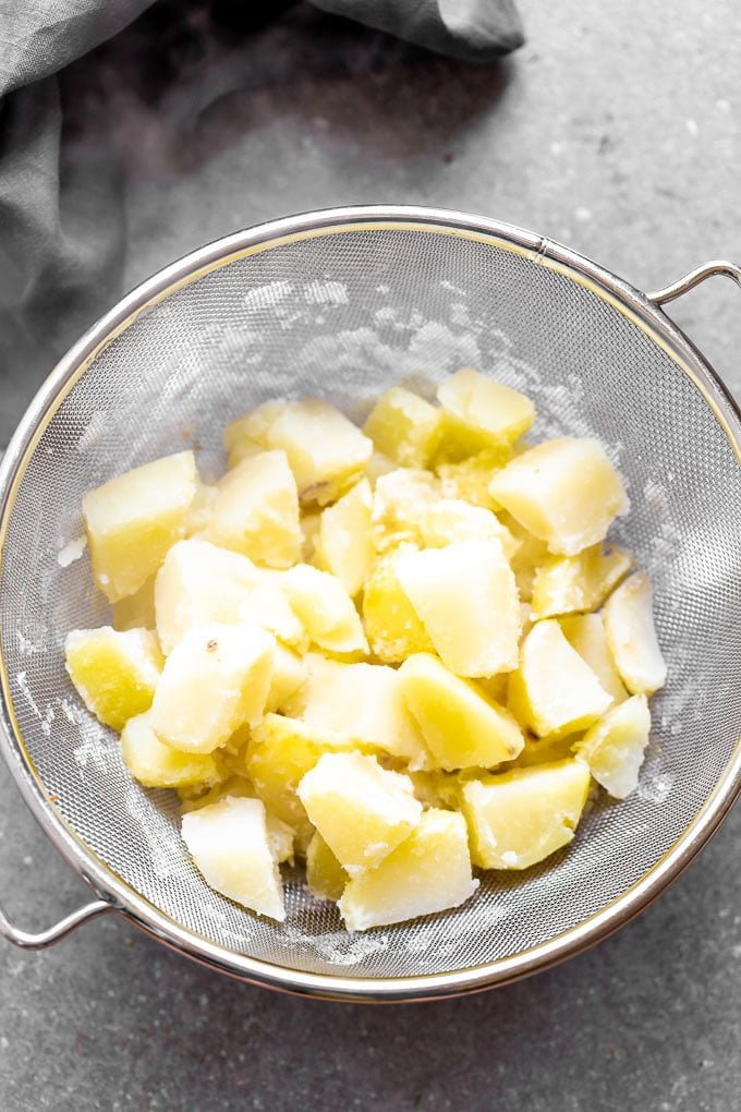 Boil potatoes and let them drip of all excess moisture.