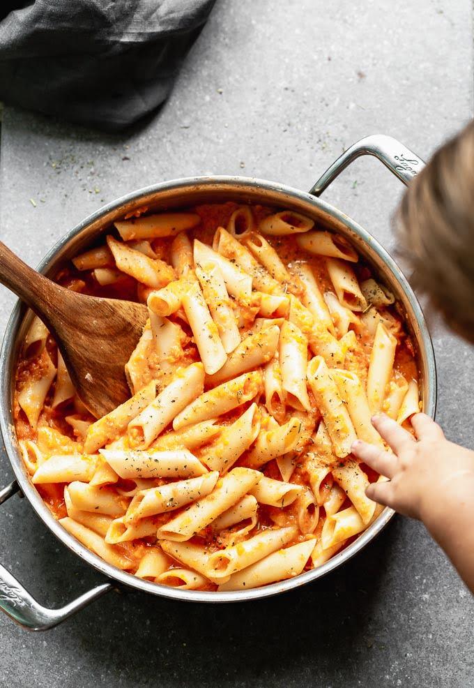 Baby helping stir creamy tomato pasta