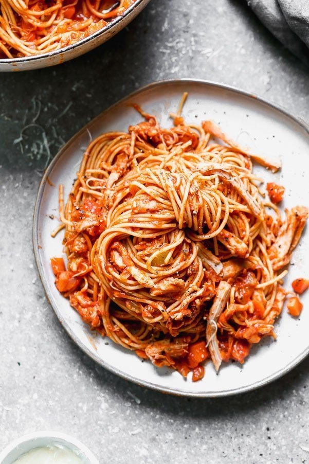 This healthy Chicken Bolognese uses chicken thighs that are slow-cooked in a red wine and a vegatable tomato sauce and tossed with whole-wheat spaghetti.