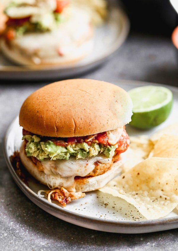 These Spicy Mexican Burgers are packed with all the best classic taco components. Spicy, smoky chicken patties, covered in gooey pepper jack cheese and smothered with smashed avocado, hot salsa, and crunch tortilla chips.