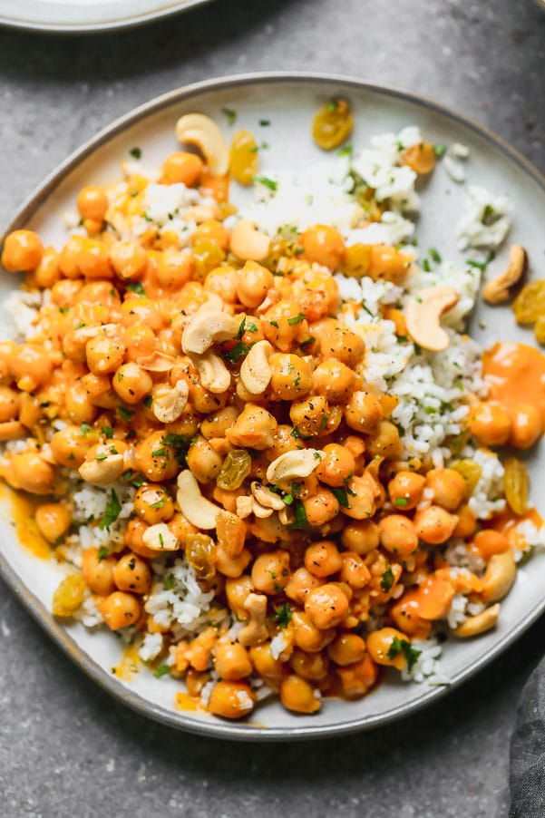 This Chickpea Vegetable Curry is what meat-free dreams are made of. Hearty chickpeas are simmered in a super easy red curry and coconut sauce until they're soft and infused with the rich flavor. The saucy chickpeas are served over a bed of jasmine rice studded with golden raisins, crunchy cashews, and lots of chopped cilantro.