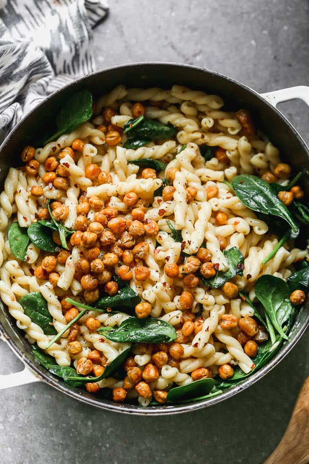 Pasta e Ceci Alla Romana (Pasta with Chickpeas) is a light, hearty, and healthy pasta dish. Aldente gemelli pasta is tossed with garlic, lemon, plenty of crushed red pepper flakes and just enough starchy pasta water to make a light sauce. It's also packed with crispy chickpeas, sweet roasted garlic and tender spinach leaves.
