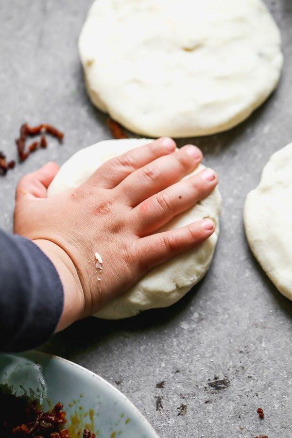 Flatten pupusas with hand
