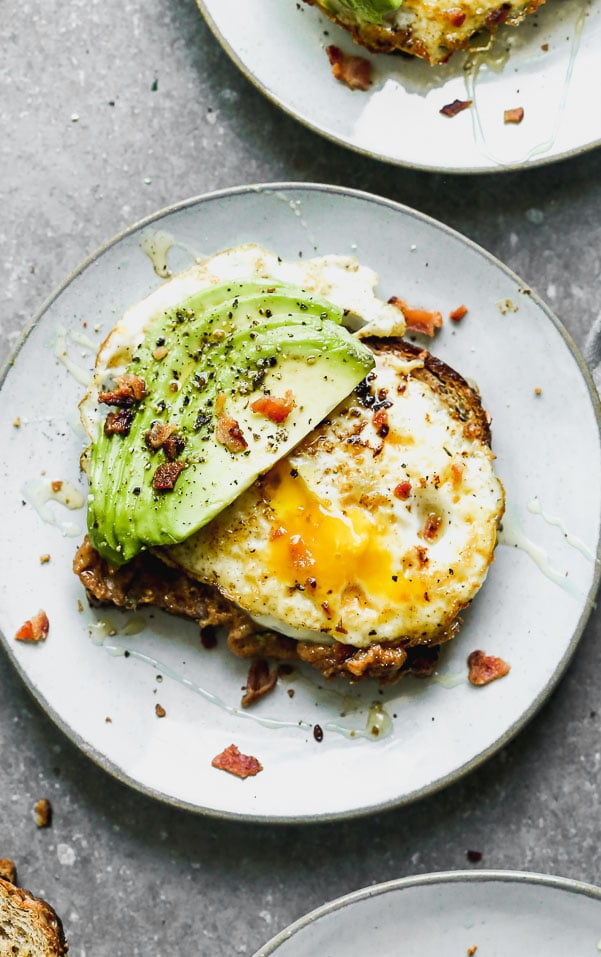 Our Favorite Avocado Toast with Egg has a couple of secret ingredients that make it different than most of the avocado toast recipes out there. Our version is slathered with nutty almond butter, top with a fried egg, lots of thinly sliced avocado, and then sprinkled with crumbled bacon and a little drizzle of honey and sea salt. It's the perfect medley of sweet, salty, and savory, and we can't get enough of it!