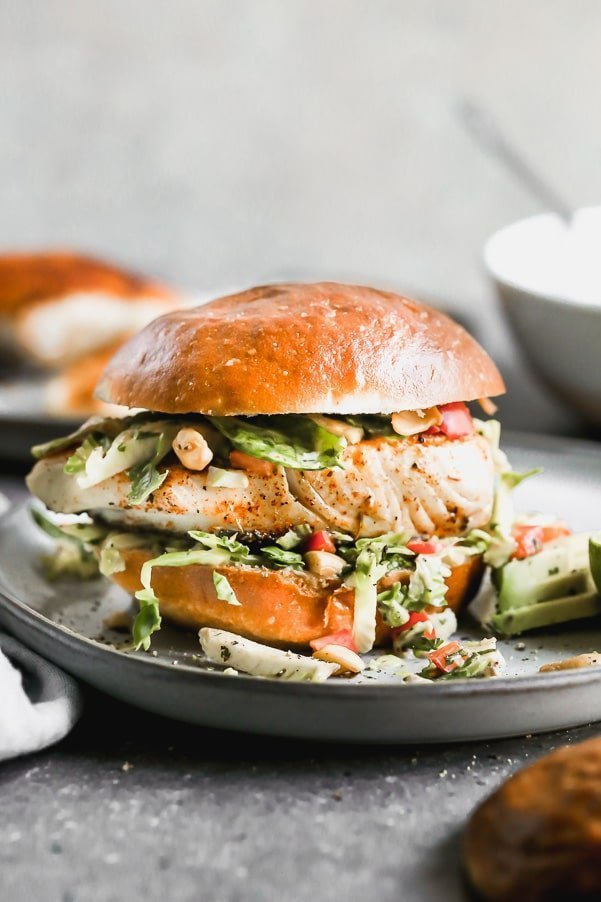 If you want a little taste of vacation, try out our Blackened Fish Sandwich Recipe. This easy fish sandwich is pan-seared until crusty and blackened on the top and flaky inside, nestled into a brioche bun, and topped with a lime and cumin Brussels sprout slaw.