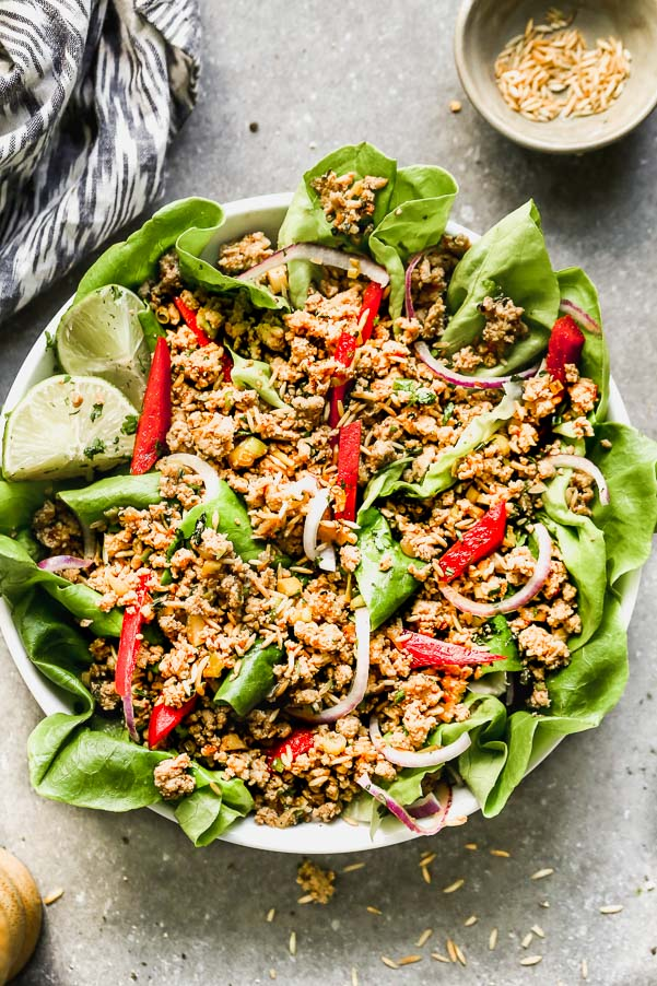 This Easy Chicken Larb Salad is the most FLAVORFUL meal. Ground turkey or chicken is tossed with zesty lime juice, fish sauce, and spicy chili sauce, served over a bed of mixed greens, red bell peppers, and red onion, and topped off with crispy toasted rice. Hearty, healthy, and so delicious.