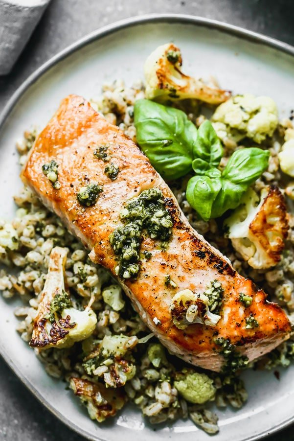 Salmon with Pesto and Roasted Cauliflower is an easy 5-ingredient full dinner! Yep, all you need is just five ingredients to create the crispiest, most flavorful salmon meal. We pan-sear salmon filets in a screaming hot cast iron skillet, and serve it over a bed of pesto farro studded with nutty roasted cauliflower. This is honestly the BEST five-ingredient meal you'll ever make!