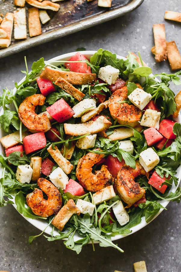 Blackened Shrimp and Halloumi Salad - have you seen a prettier combination? We take take peppery arugula leaves and toss them in a simple vinaigrette and then layer them with sweet watermelon, salty halloumi cheese, toasted pita croutons, and spicy blackened shrimp. It's hearty, healthy, and SO delicious.
