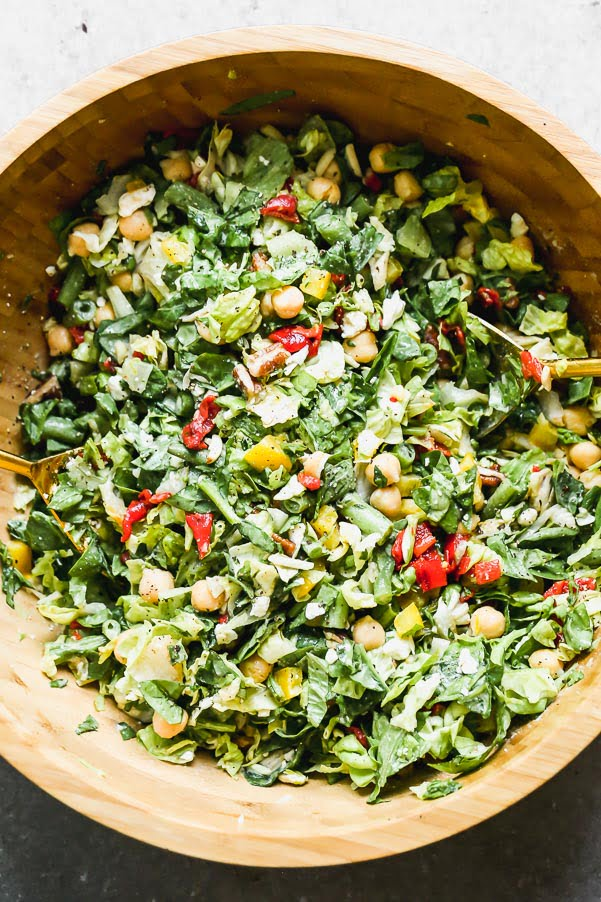 This easy throw-it-together chopped chickpea and tahini salad is hearty and healthy thanks to the addition of chopped green beans, bell peppers, spinach, roasted red peppers, and chickpeas. We add in slivered almonds and pecans for a little bit of crunch and toss everything in an easy lemon and tahini dressing.