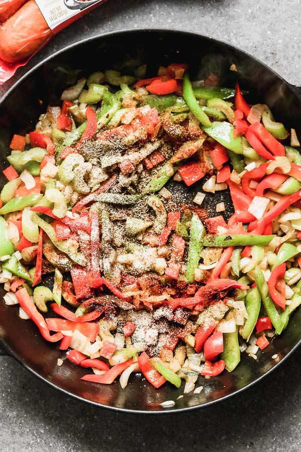 Sauté green peppers, red peppers, onions, and spices.