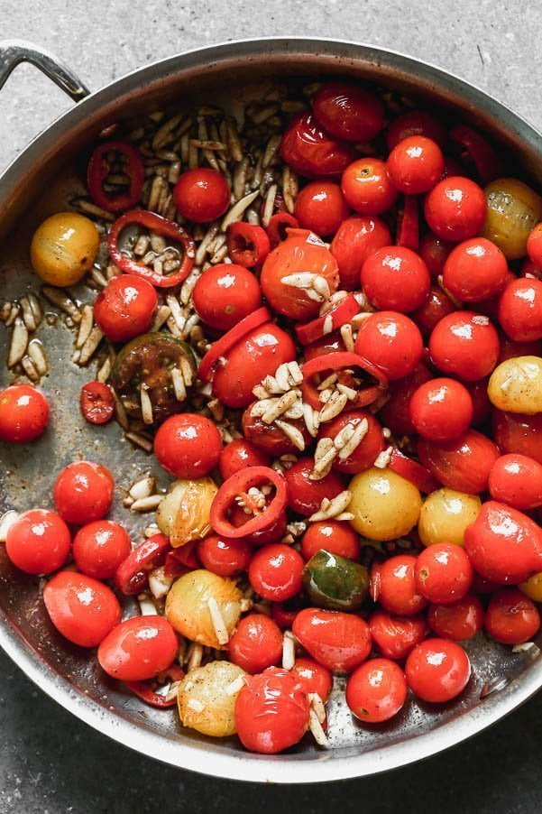 Cook cherry tomatoes and fresno chili peppers with brown butter, almonds, and garlic.