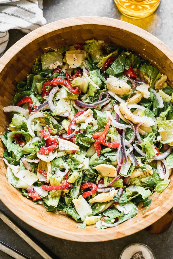 Italian Artichoke Salad is our go-to salad for cozy winter dinners, alfresco summer barbecues and everything in between. We marinate artichoke hearts and red onions in a zippy red wine and parmesan vinaigrette, toss everything with crisp romaine lettuce and sliced roasted red peppers. Easy to make ahead of time, perfect to feed a large family, and delicious.
