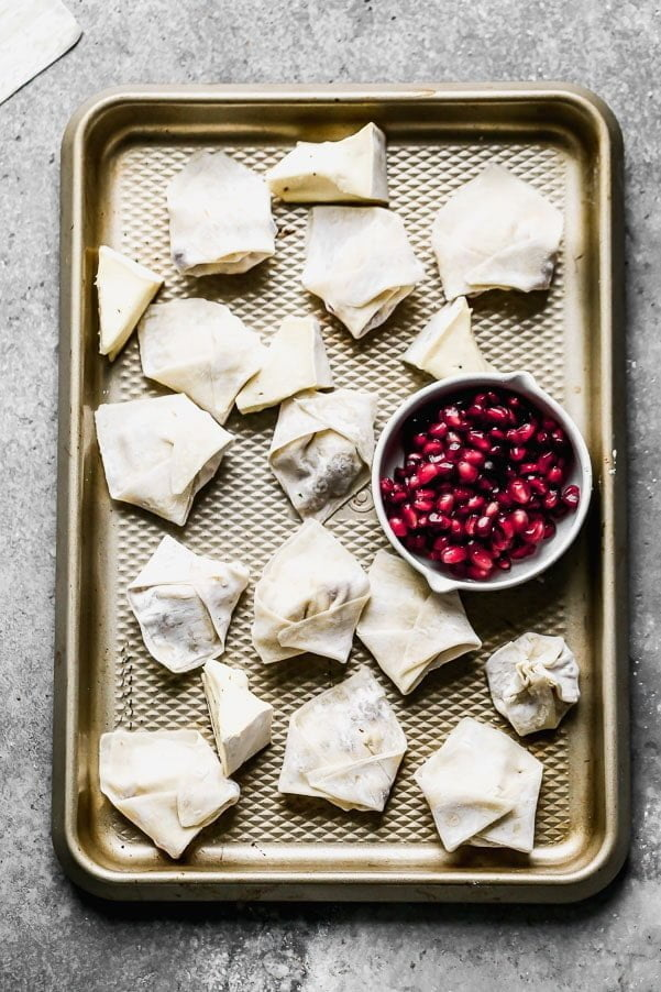 Fold wontons to wrap around brie and pomegranate