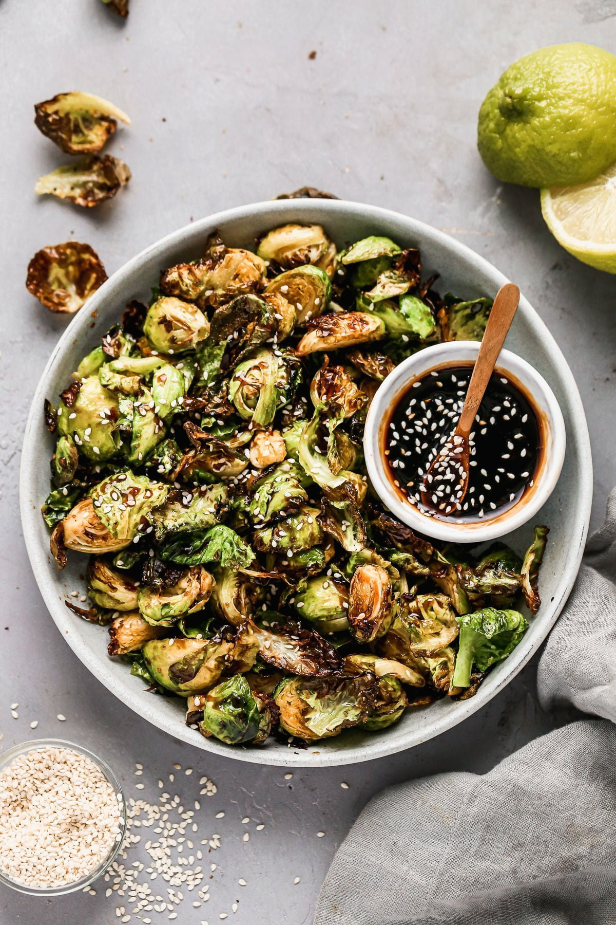 Crispy on the edges, soft on the inside, and dusted with the perfect amount of seasoning, our Air Fryer Brussels Sprouts are the perfect quick and easy veggies to make any night of the week. Once the Brussels sprouts are done in the air fryer we toss them in a sticky homemade honey soy glaze, sprinkle with sesame seeds and then serve with extra sauce for dipping. (You'll want to dip.)