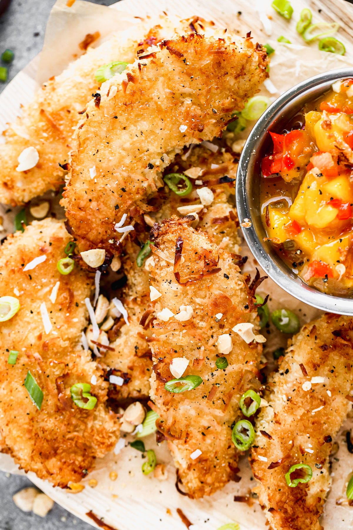 Let's all satisfy the kid in us with these ultra crispy, completely irresistible Baked Coconut Chicken Tenders. We coat tender chicken in a light coconut and panko breading, bake them on a screaming hot baking sheet and then serve them with a quick warm mango salsa and a hot honey drizzle.