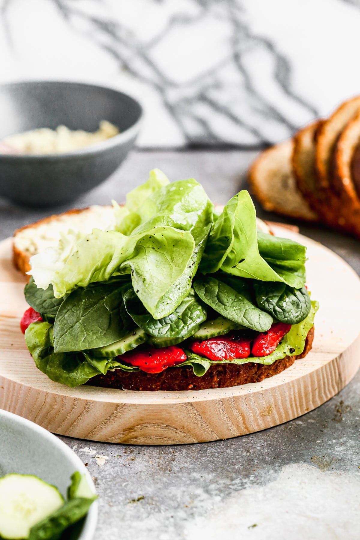 Our take on a classic Cucumber Sandwich includes layers of hearty spinach, vinaigrette-dressed butter lettuce, smoky roasted red peppers, and the pièce de résistance, a pistachio-infused goat cheese that will make you weak in the knees. The perfect lunch to prep early and enjoy all week long.