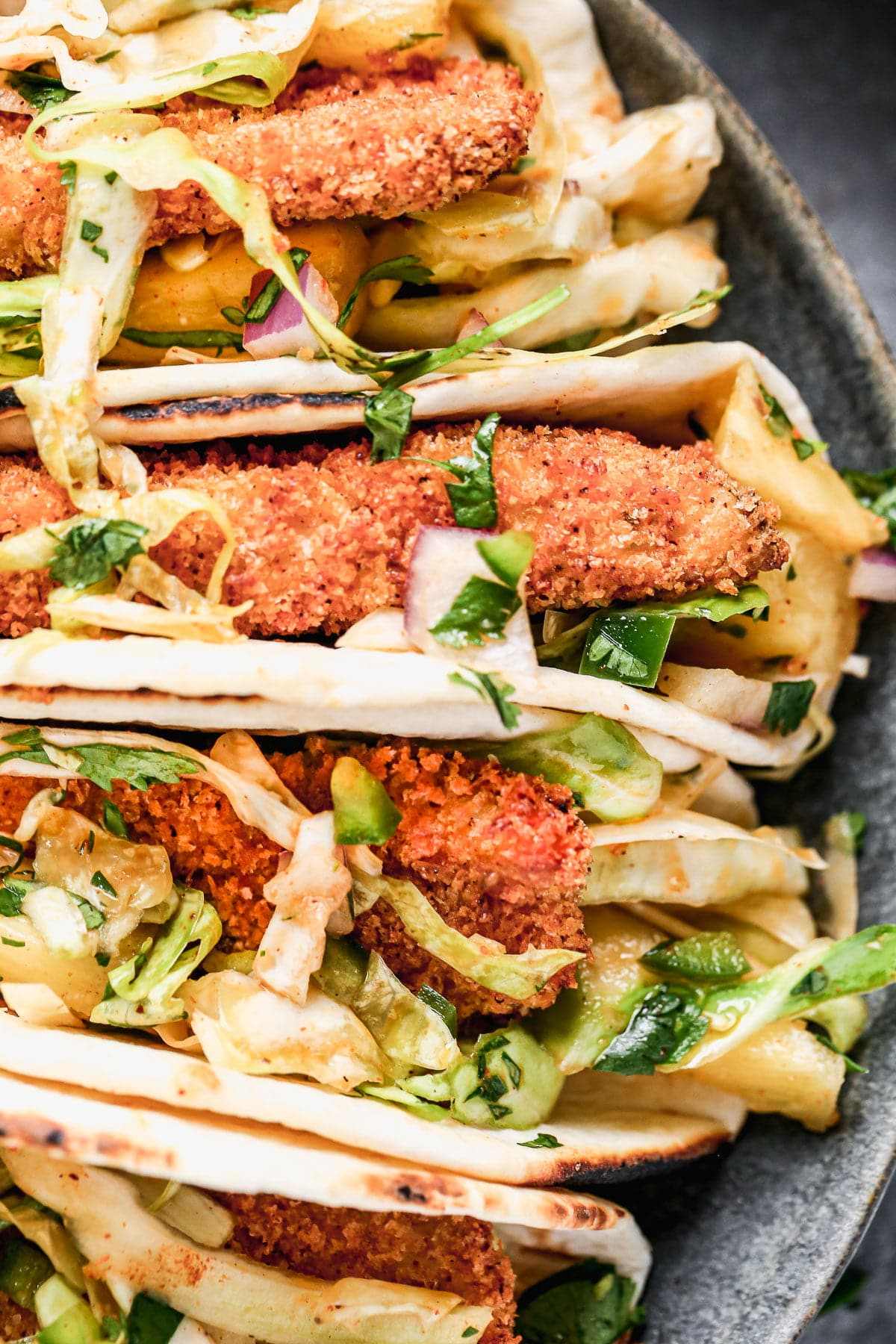 Never have a soggy fish taco again! Our Air Fryer Fish Tacos produce the CRISPIEST breaded fish without all the fat and calories and WITH all the flavor. We nestle the crunchy barramundiin charred street taco tortillas, top with a quick pineapple slaw, and a fresh squeeze of lime juice.