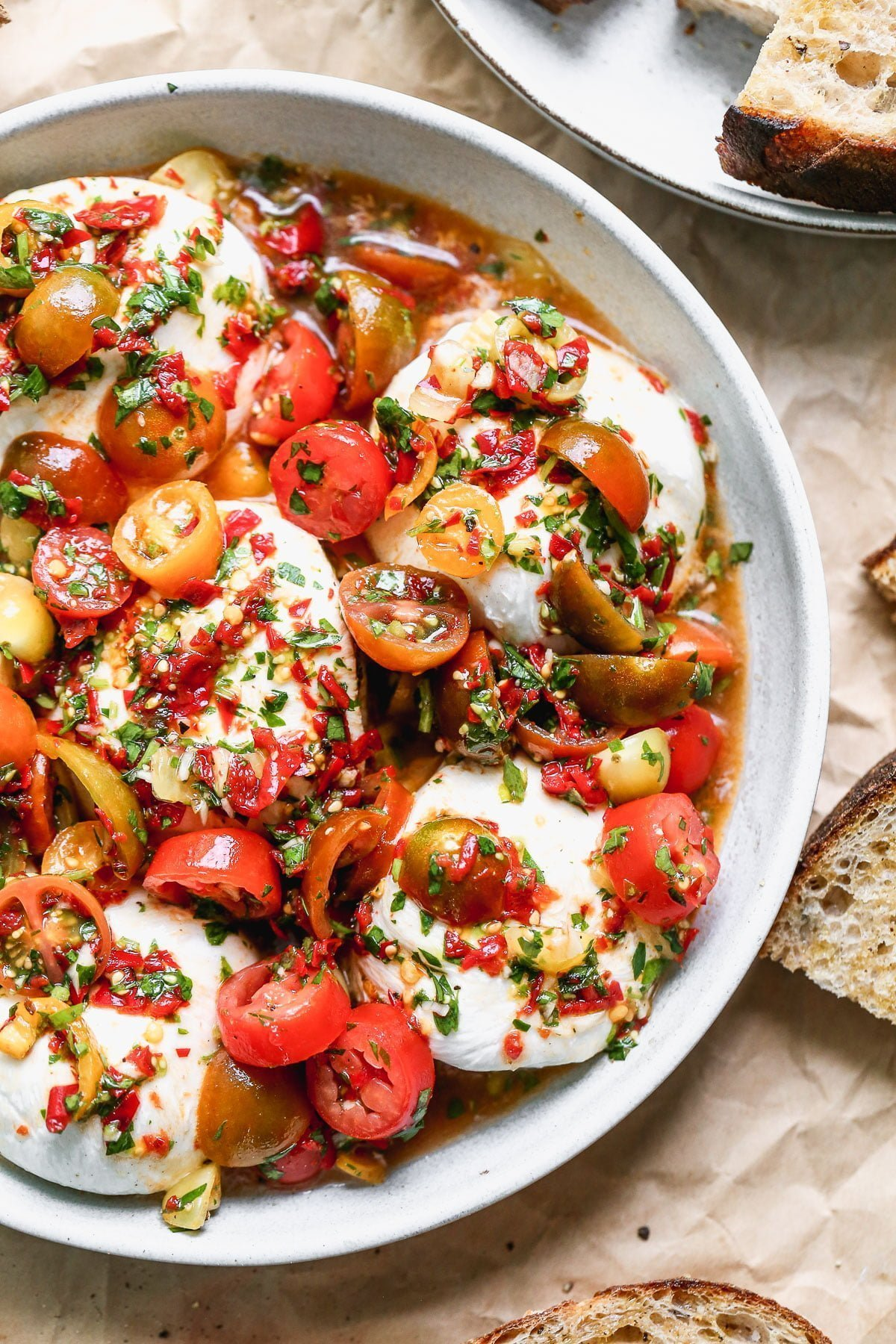 This Calabrian Chili and Burrata Appetizer is going to be the star of all your summer gatherings. This is basically a classic bruschetta but so so much better. We take juicy heirloom cherry tomatoes and toss them with fiery calabrian chilis, zippy red wine vinegar, parsley, garlic, and a few briny capers. We spoon it over the most adorable mini creamy burrata balls and serve with crusty bread to soak up every juicy bite.
