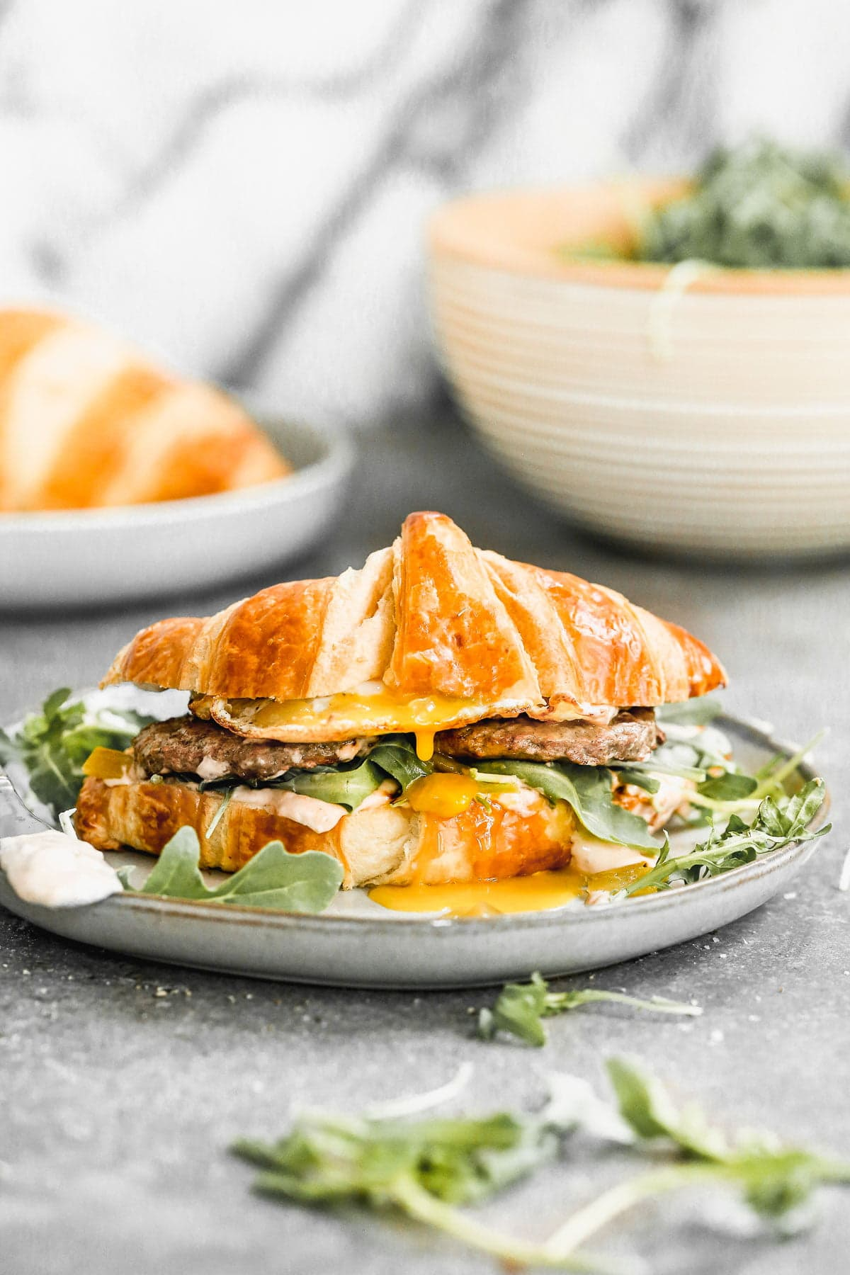Calling all breakfast lovers! Our Croissant Breakfast Sandwich is slathered with a spicy salsa cream cheese, topped with smoky green chiles, peppery arugula, salty Turkey Sausage, and of course, a drippy over-easy egg. Hearty, messy, and oh-so delicious.